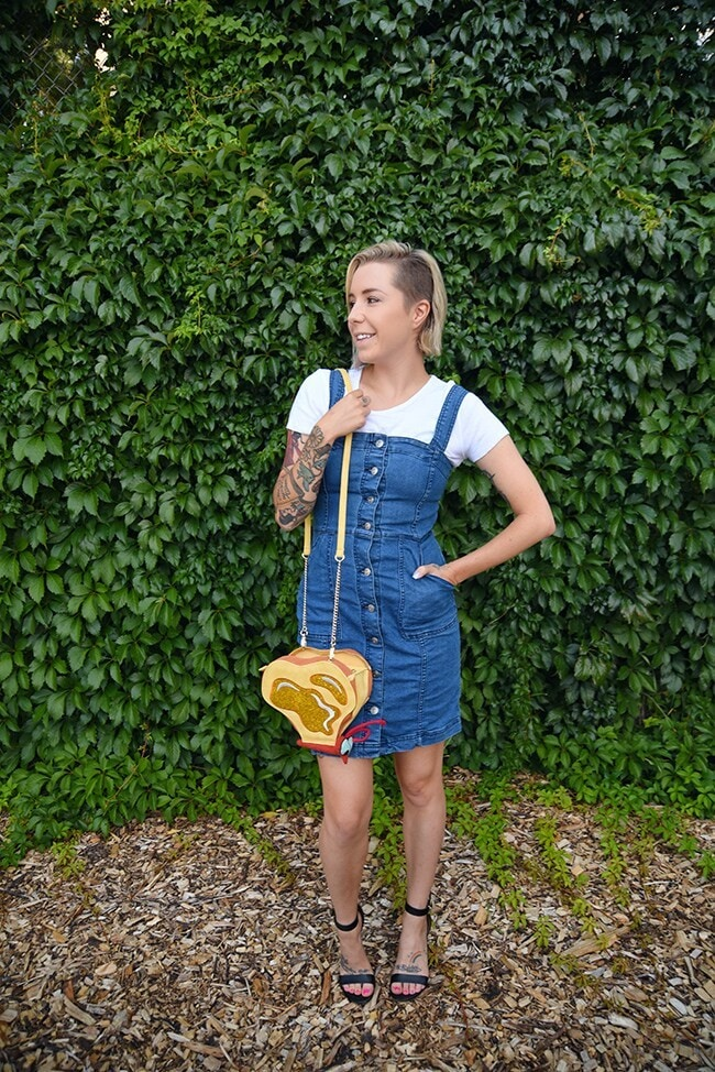 woman's purse that looks like a butterfly composed of pieces of toast with butter on it. The woman is wearing a denim overall dress