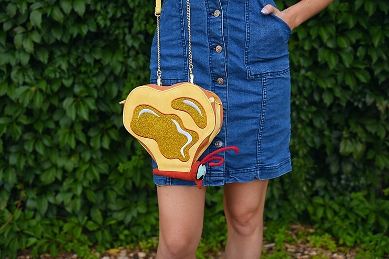 A close-up of a woman's purse that looks like a butterfly composed of pieces of toast with butter on it. The woman is wearing a denim overall dress