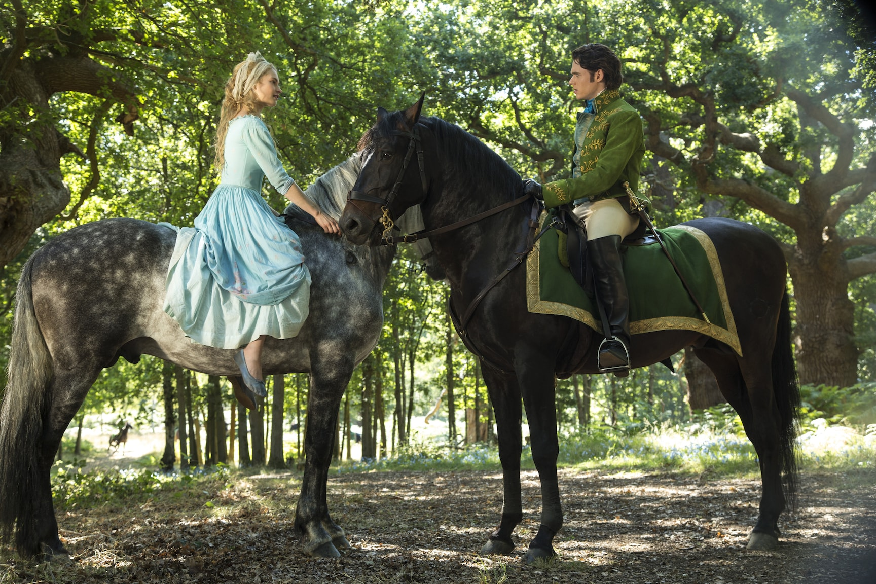 Actors Richard Madden (as the Prince) and Lily James (as Cinderella) on horseback in the movie Cinderella.