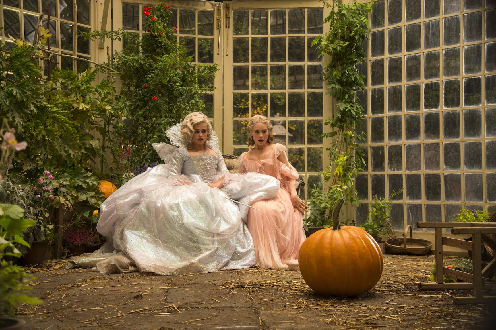 Actors Helena Bonham Carter (as the Fairy Godmother) and Lily James (as Cinderella) staring at a pumpkin in the movie Cinderella.