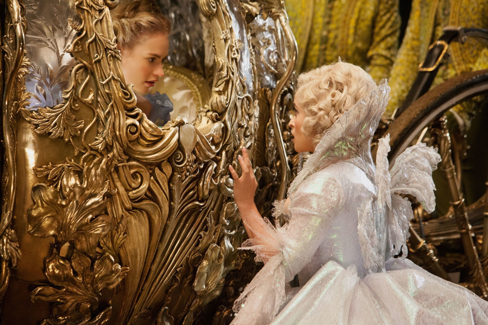 Actor Lily James (as Cinderella) in a carriage and actor Helena Bonham Carter (as the Fairy Godmother) waving in the movie Cinderella.