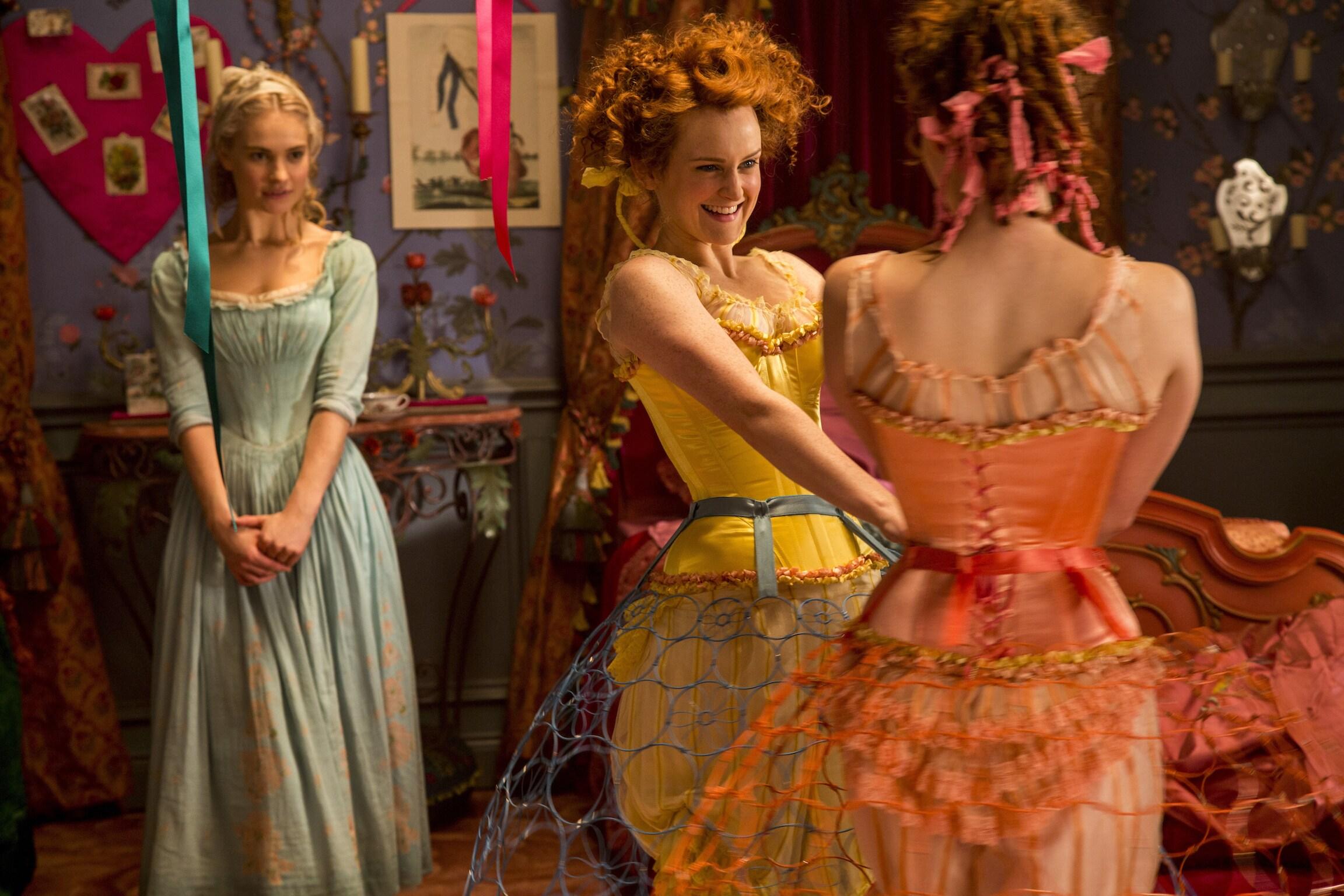 Actors Holliday Grainger (as Anastasia), Sophie McShera (as Drisella), and Lily James (as Cinderella) in the movie Cinderella.