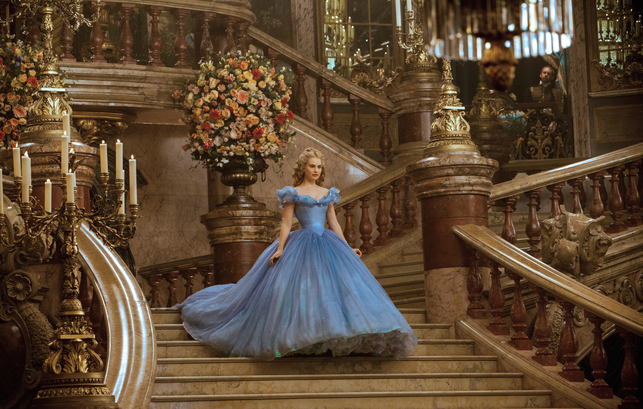 Actor Lily James (as Cinderella) walking down a staircase in the movie Cinderella.