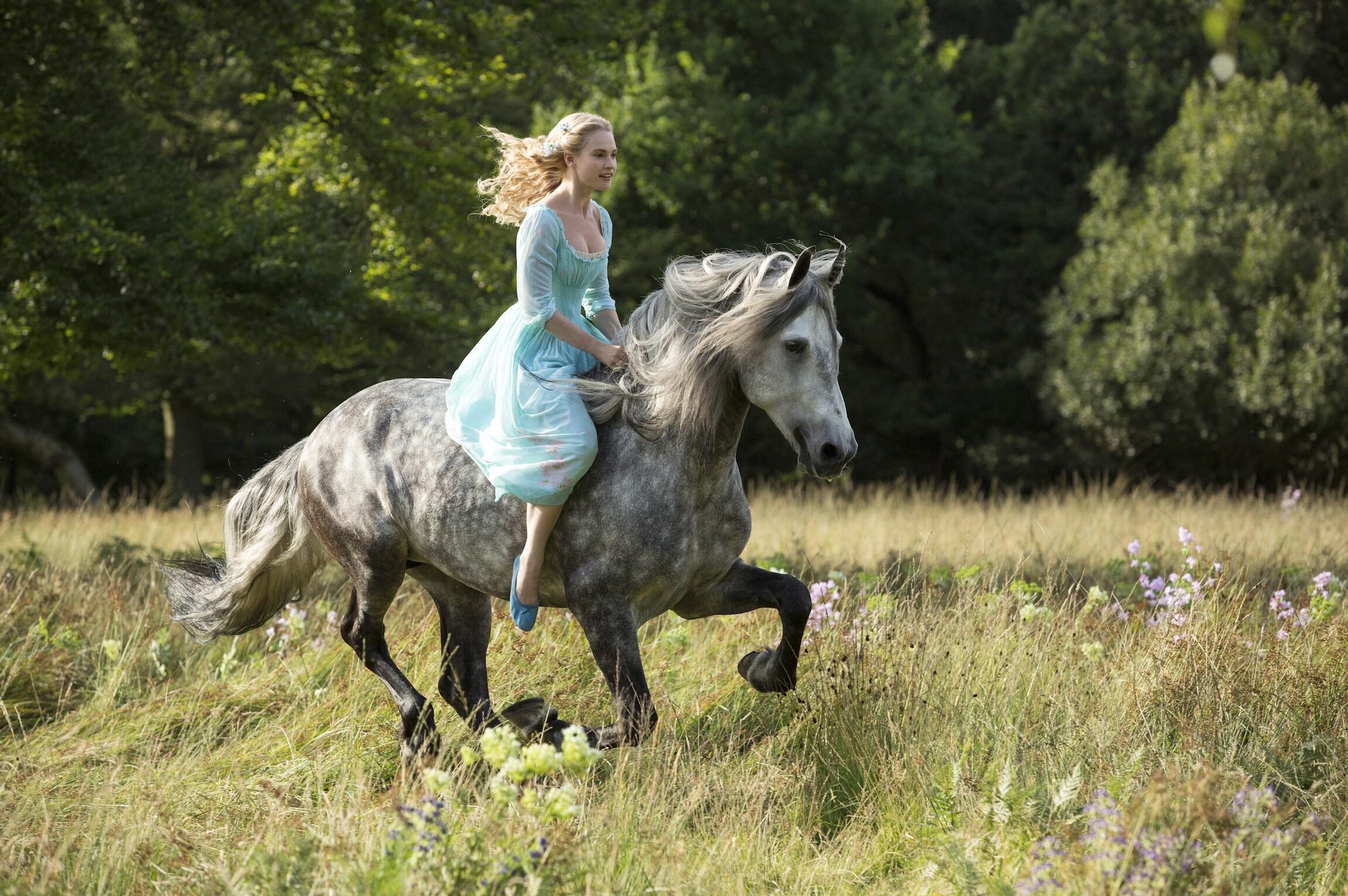 Actor Lily James (as Cinderella) on horseback in the movie Cinderella.