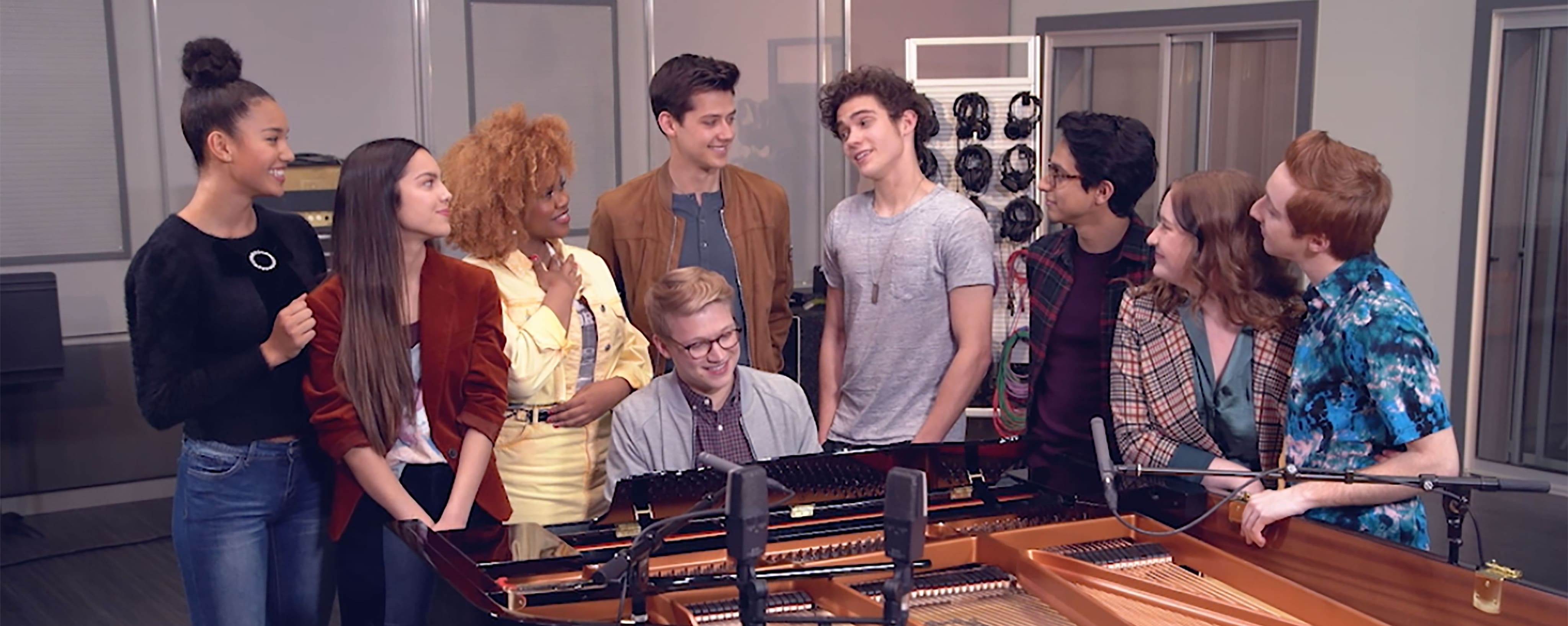 Cast of High School Musical: The Musical: The Series singing at a piano.
