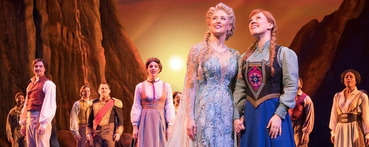 Anna and Elsa from Frozen on Broadway stand on the stage looking into the light with the cast of Frozen on Broadway.