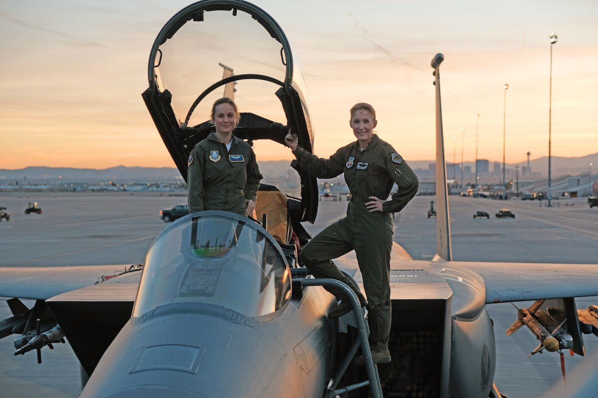 Brie Larson as Carol Danvers stands on a fighter plane with another woman, as the sun sets in the background in a scene from Marvel Studios' Captain Marvel.