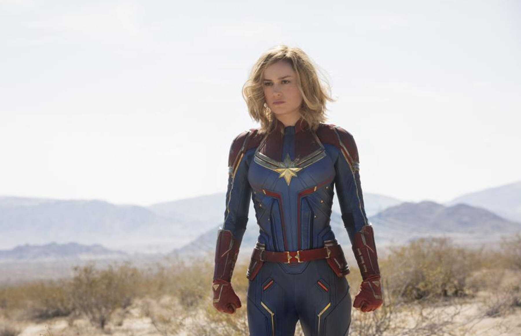 Bri Larson as Captain Marvel in Blue and red costume with gold trim in the desert