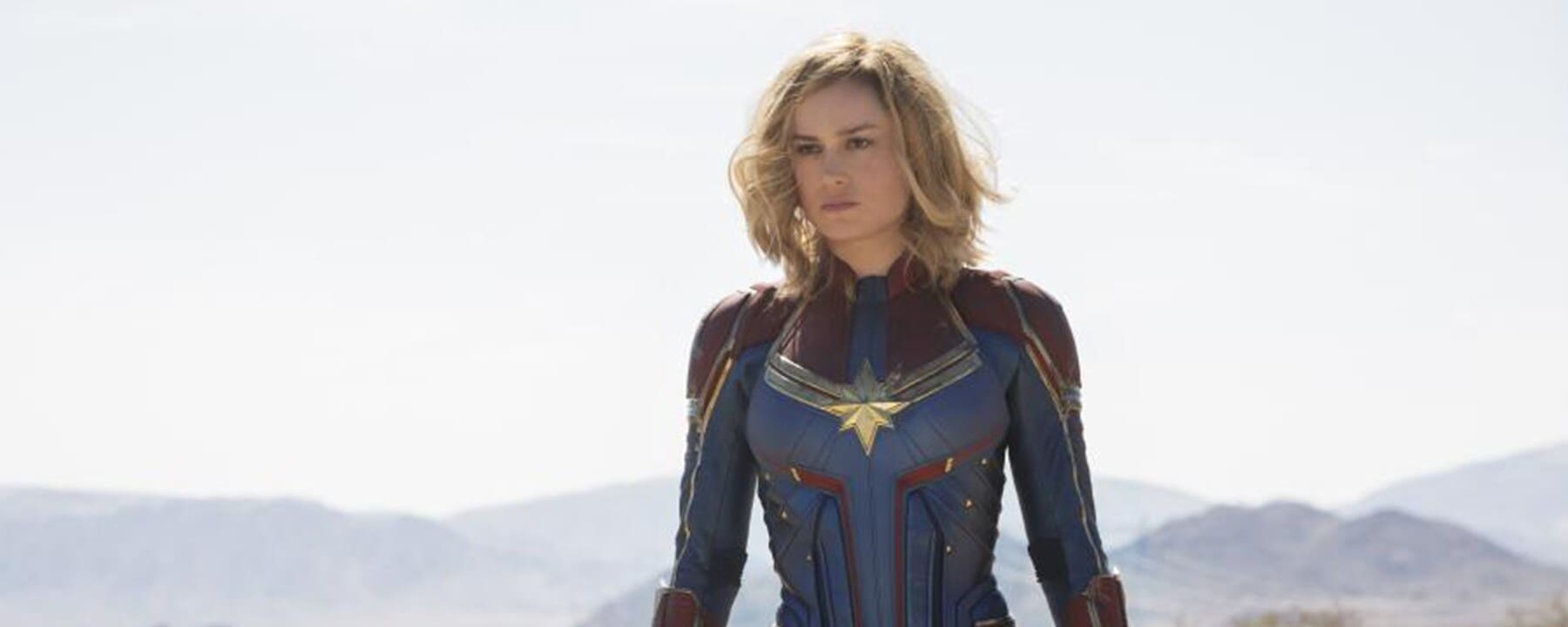 Captain Marvel wearing Blue and Red suit with gold trim in the desert.