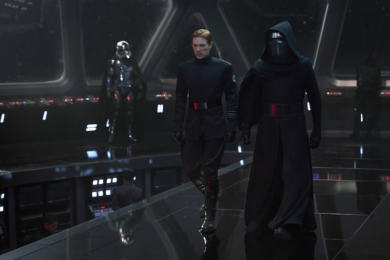 Captain Phasma standing in a command bridge as Kylo Ren and General Hux strategize
