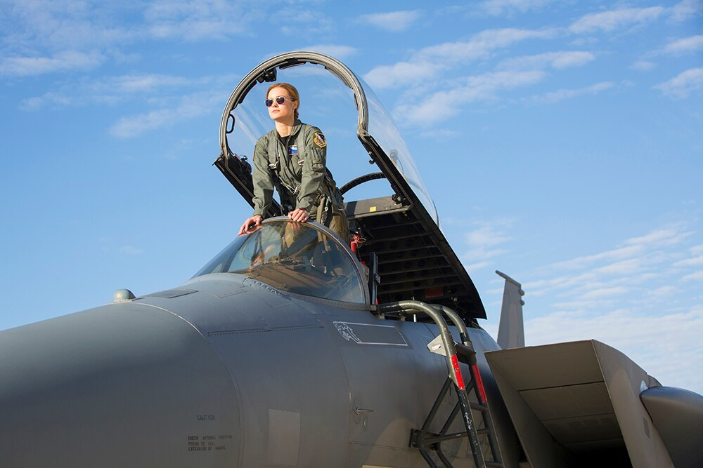 Carol Danvers (Captain Marvel) wearing flights suit and aviators in the cockpit of a fighter jet