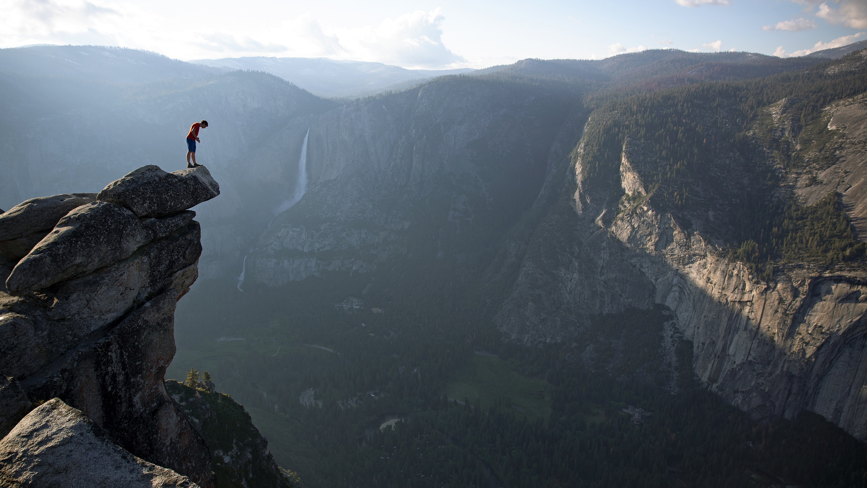 Alex Honnold peers over the edge of Glacier Point in Yosemite National Park. He had just climbed 2,000 feet up from the valley floor. (Photo by National Geographic/Jimmy Chin)