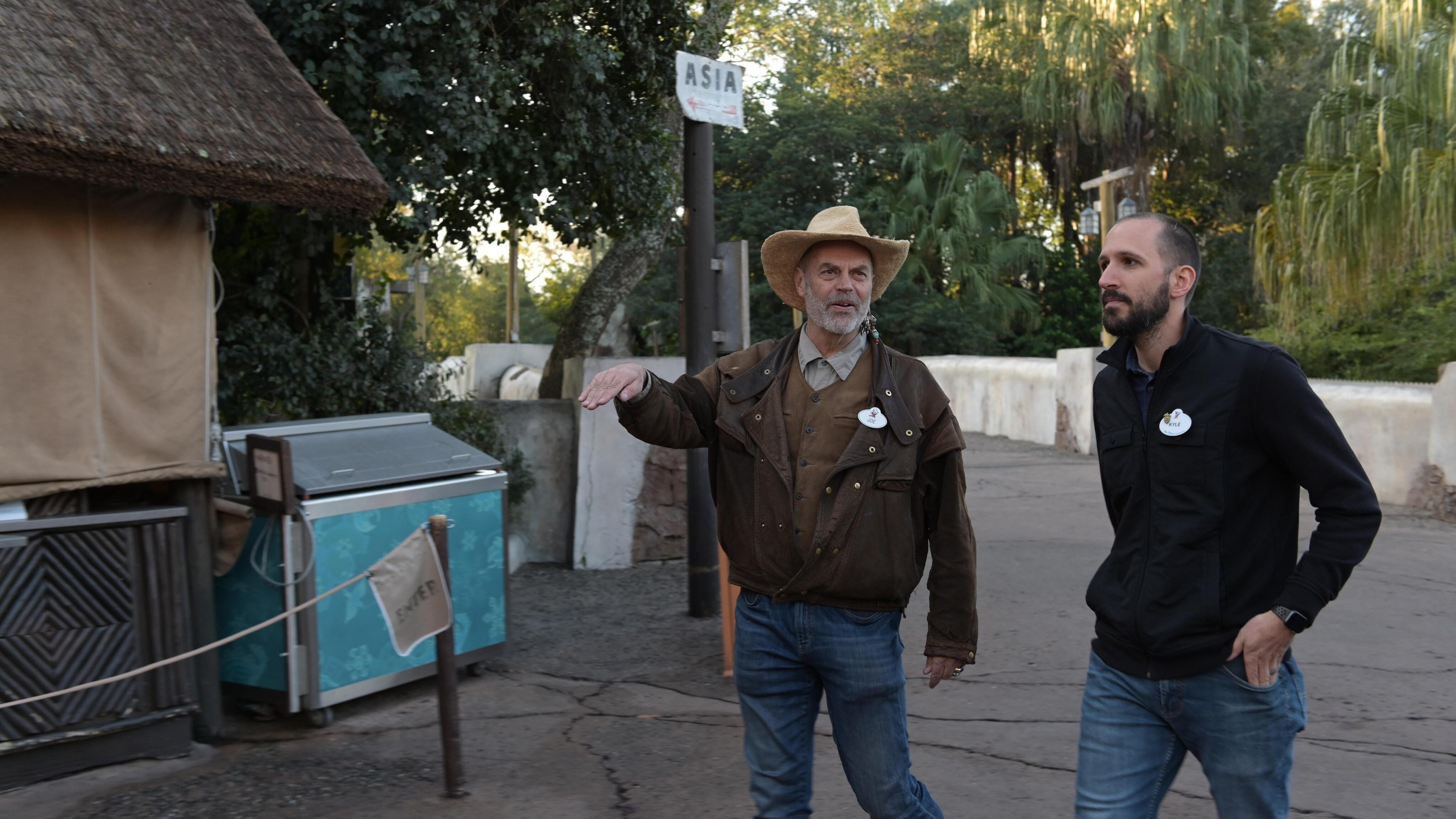 Joe Rohde (Creative Portfolio Executive Walt Disney Imagineering), Kyle Price (Art Director). Joe and Kyle walk along the park path. (Charlene Guilliams/Disney)