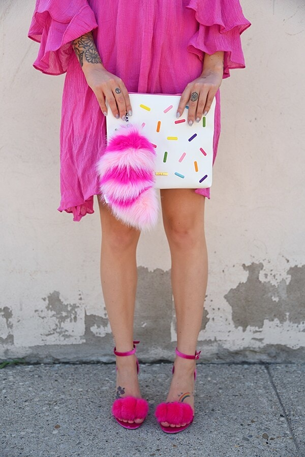 A close-up of a woman's hand holding a white clutch with a colorful sprinkle pattern. Attached to the clutch is a bright pink keychain that looks like the cheshire cat's tail from Alice in Wonderland. The woman is wearing a bright pink dress and pink shoes.