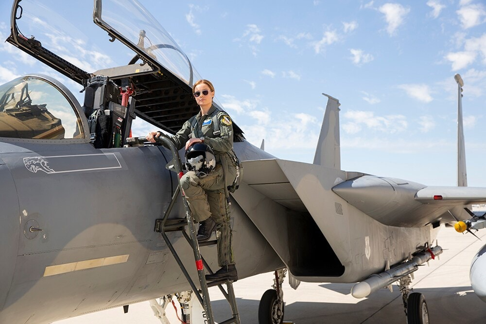 Brie Larson (Carol Danvers) on ladder next to fighter jet