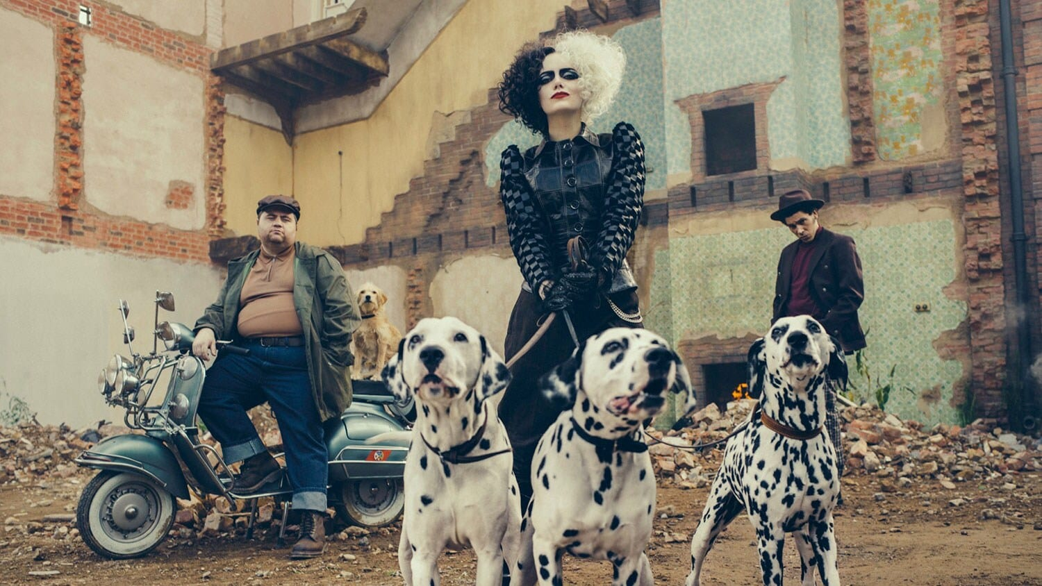 Emma Stone as Cruella de Vil holding three Dalmatians with her two sidekicks in the background