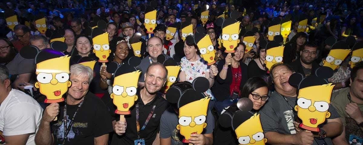 D23 audience holding Bart Simpson face signs