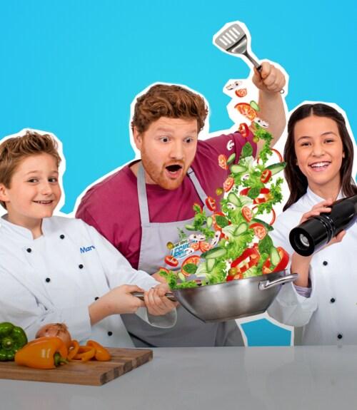 Marvin und Amalia stehen neben Koch Roland und schwenken eine Pfanne mit Gemüse