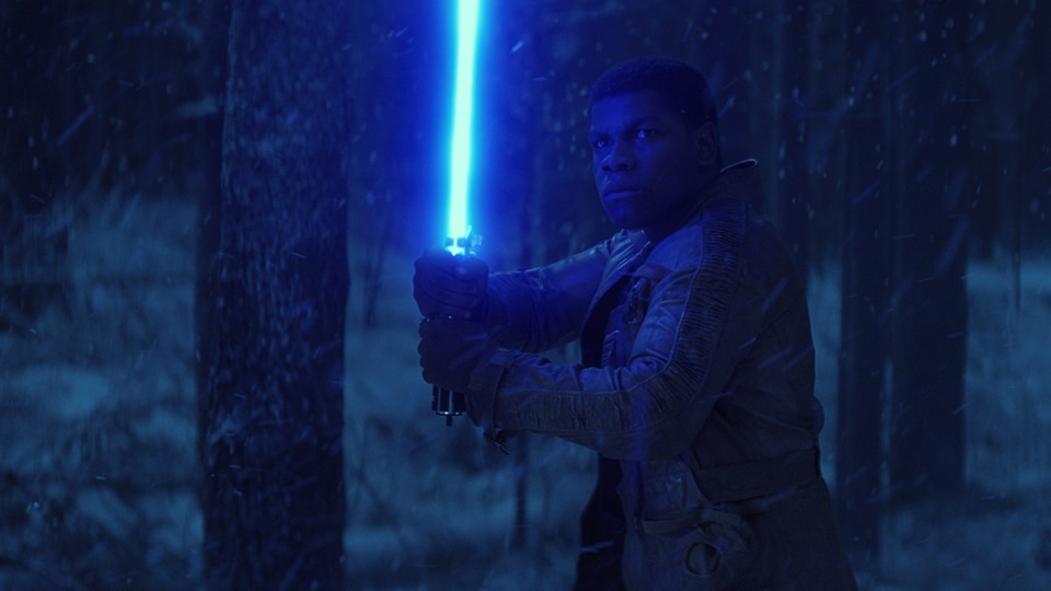 Finn with a lightsaber in the forest at night