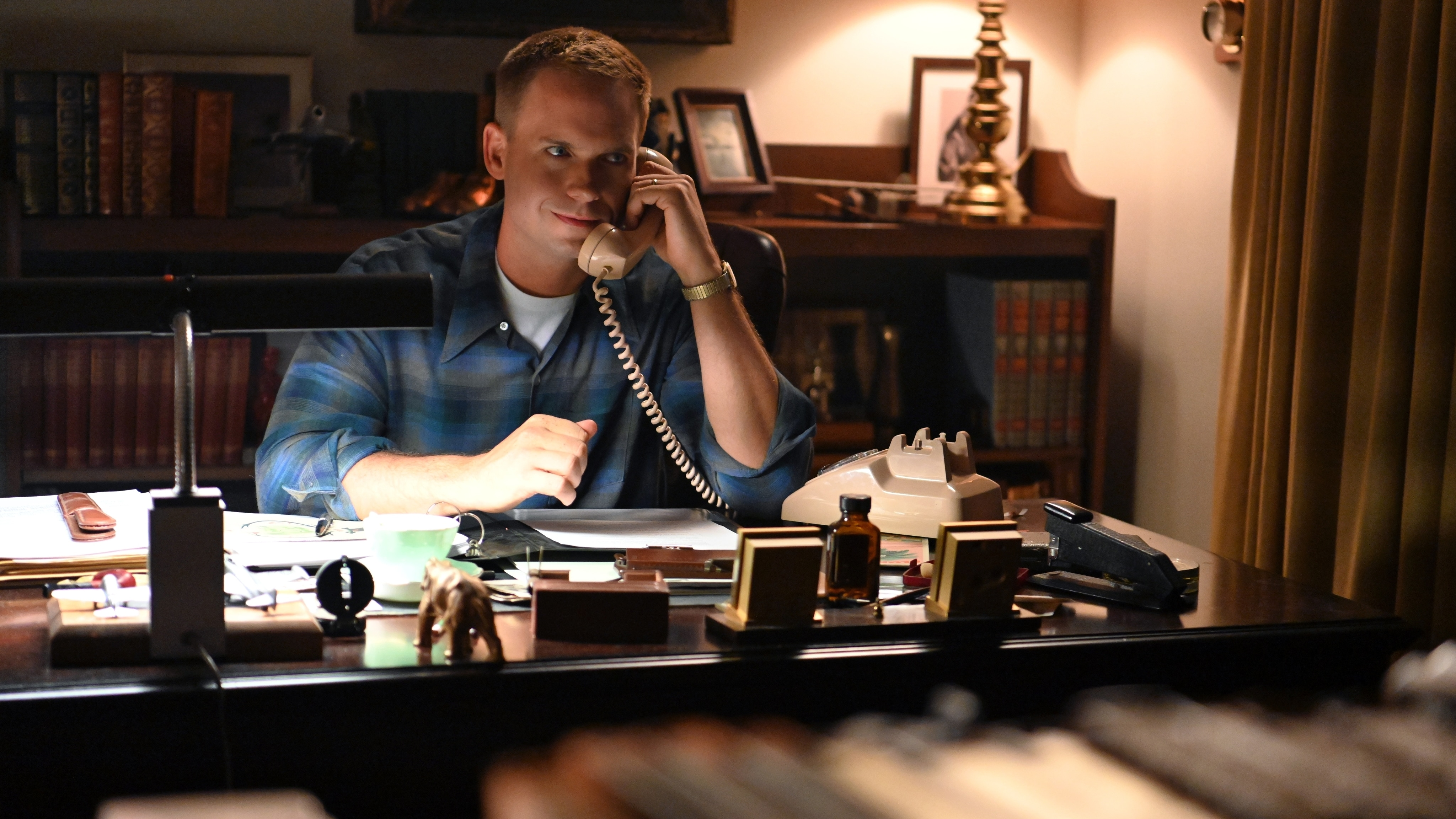 John Glenn, played by Patrick J. Adams, speaks to Bobby Kennedy on the telephone about the upcoming presidential election and the space program in National Geographic's THE RIGHT STUFF streaming on Disney+. (National Geographic/Gene Page)