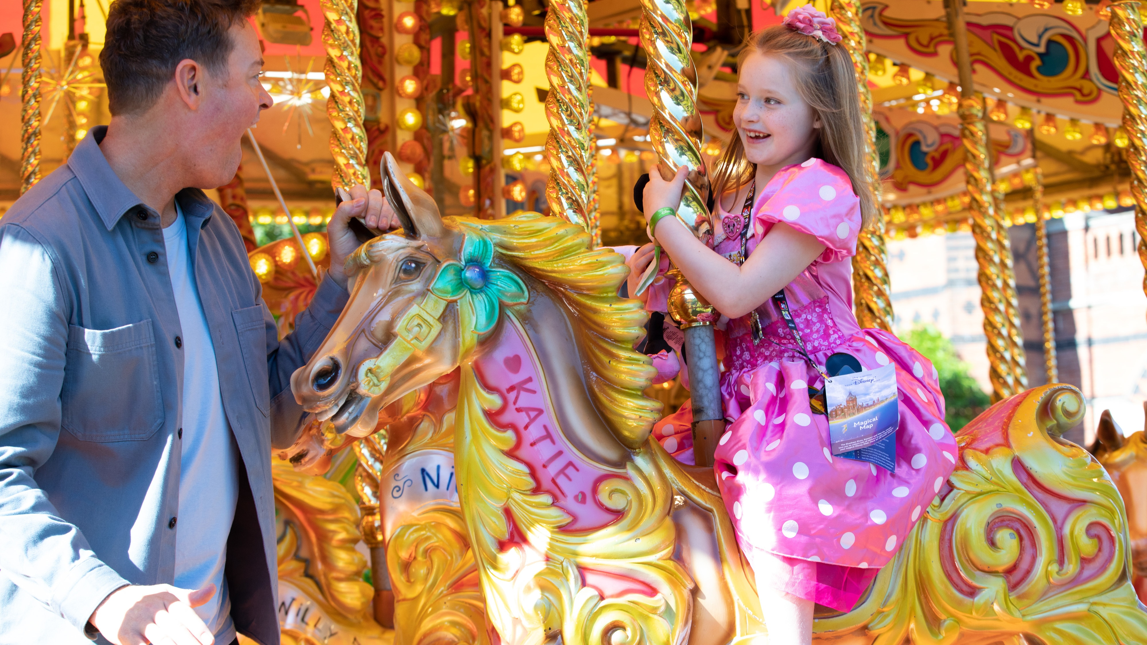 Girl riding the carousel looking at Stephen Mulhern