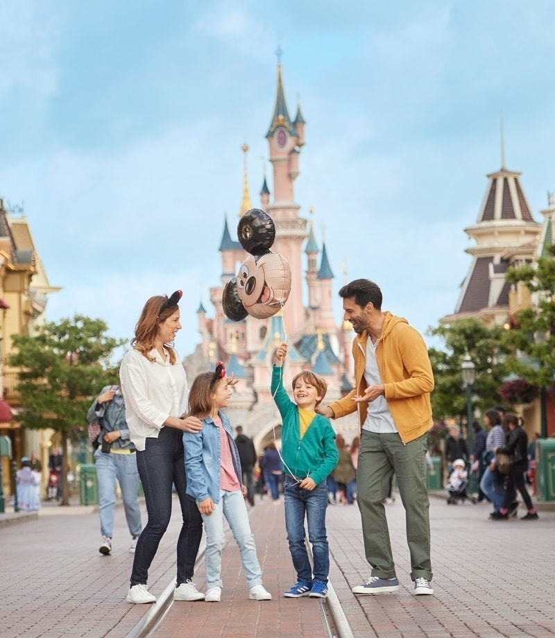 A family holding a Mickey Mouse Balloon outside Sleeping Beauty's Castle