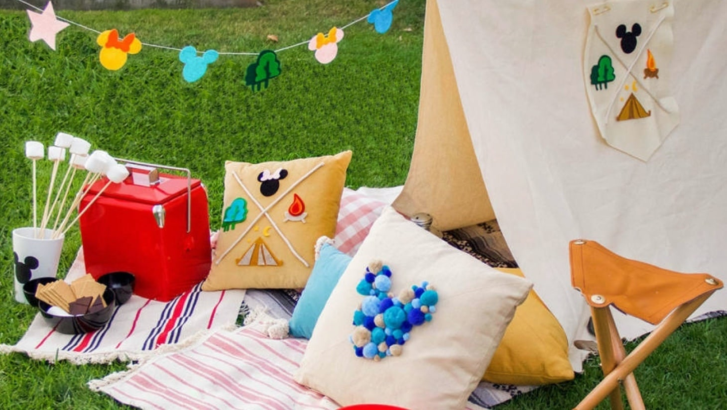 A Mickey inspired tent, cushion and snacks in a garden