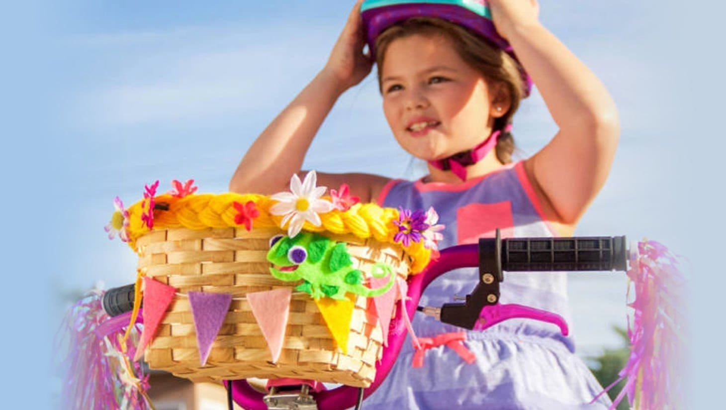 A young girl on a bike with a Tangled themed basket