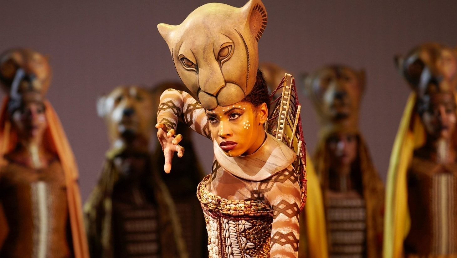 An actress performing on stage in The Lion King the Musical
