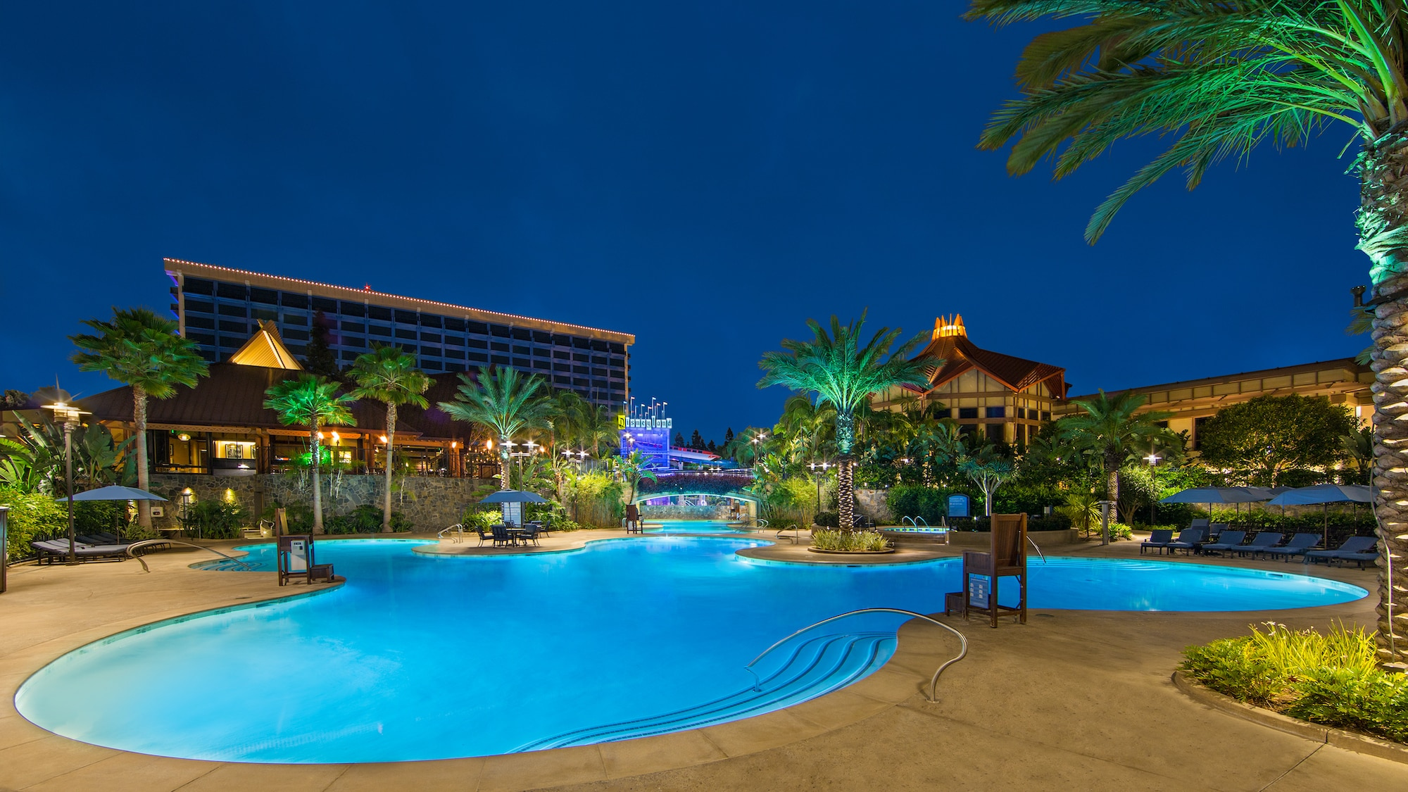 Image of the pool lit at night at the Disneyland Hotel.