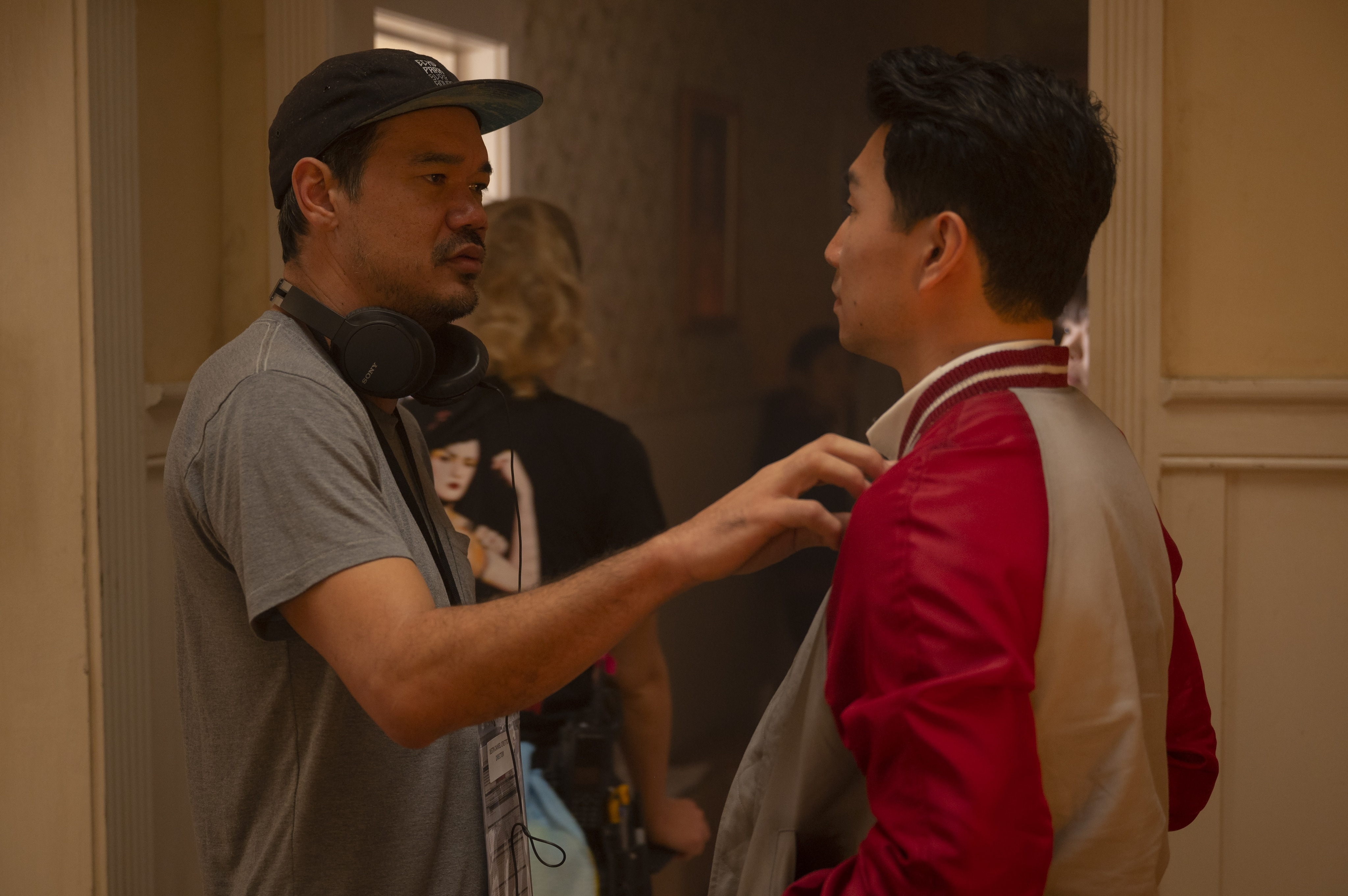 Director Destin Daniel Cretton talks with actor Simu Liu, who plays Shang-Chi, on set.