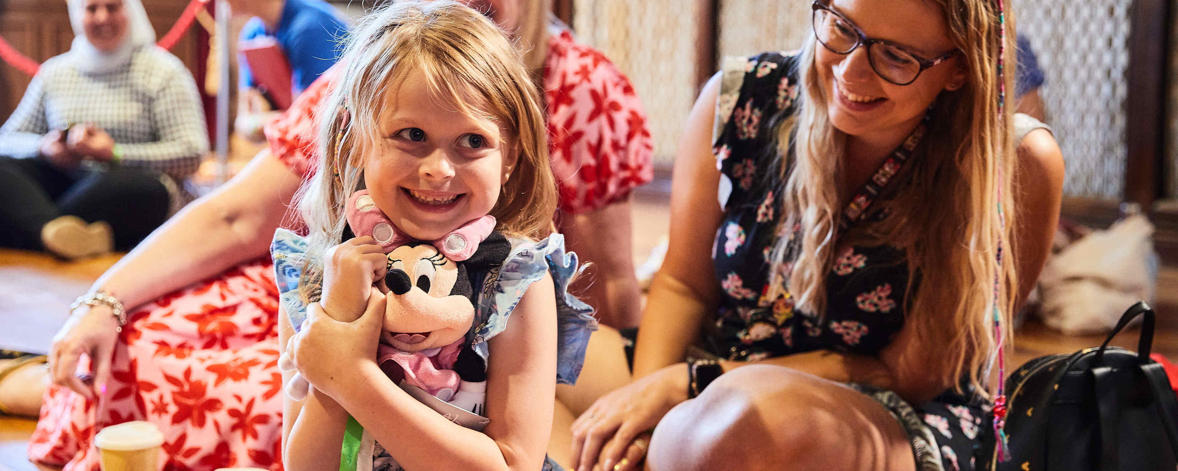 Young girl at the Wish Event with a Minnie Mouse plush