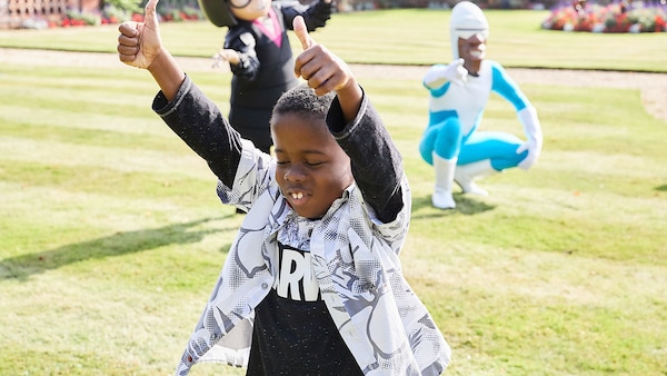 Boy playing, with Edna Mode and Frozone in the background