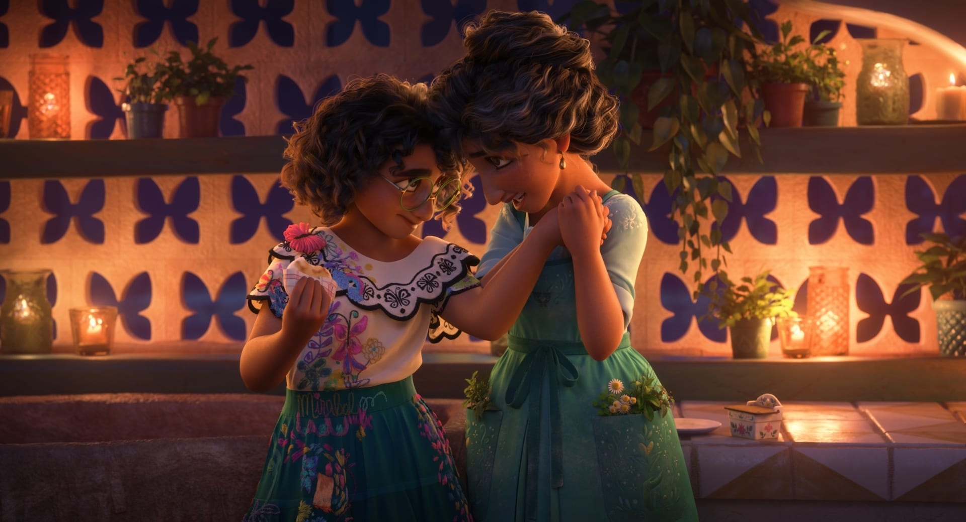 Mirabel Madrigal embraces her mom, Julieta, in Walt Disney Animation Studios' Encanto.