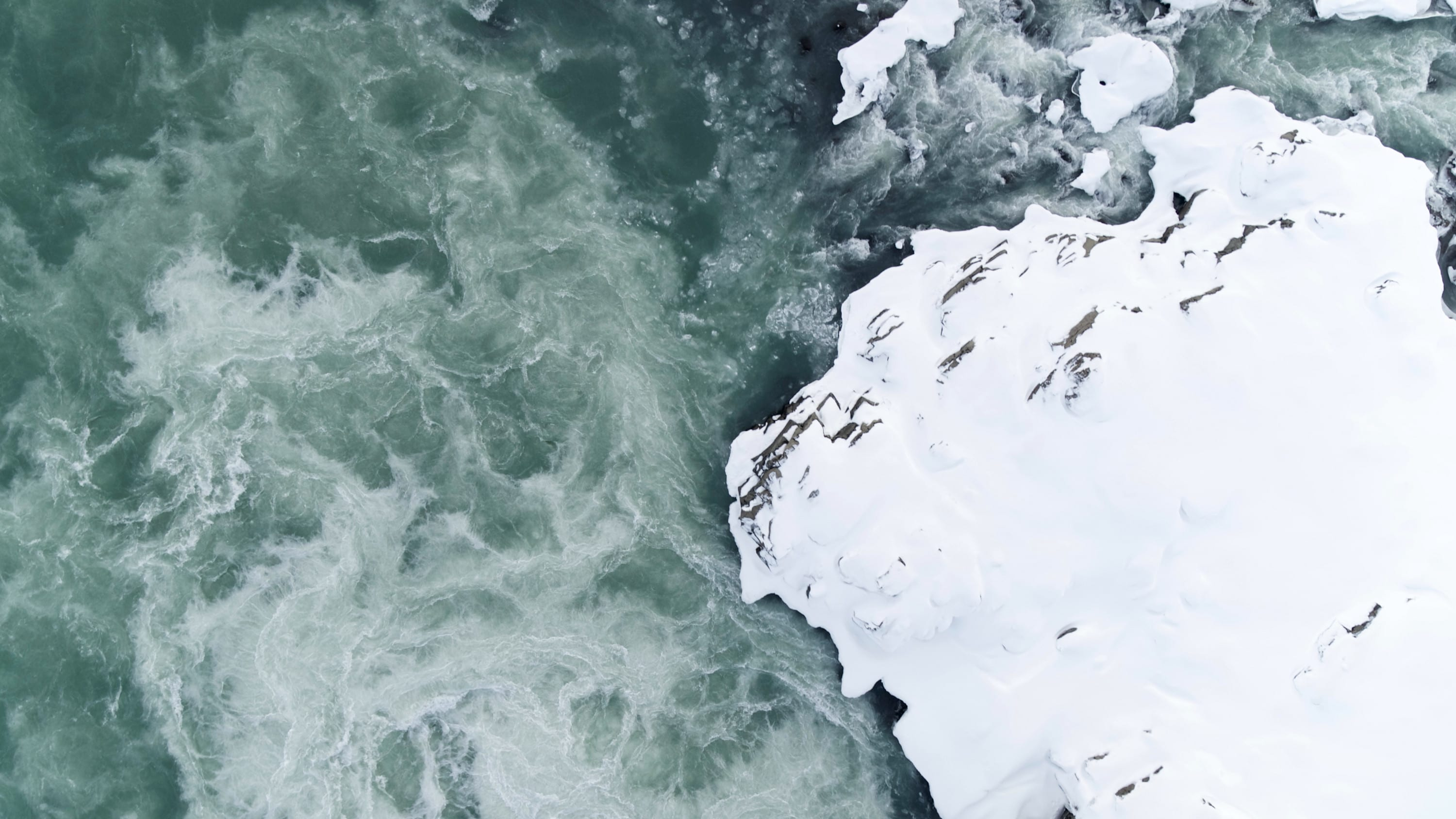 Aerial view of a flowing icy river with a snow-covered riverbank in Jökulsárlón National Park, Iceland. (National Geographic for Disney+)