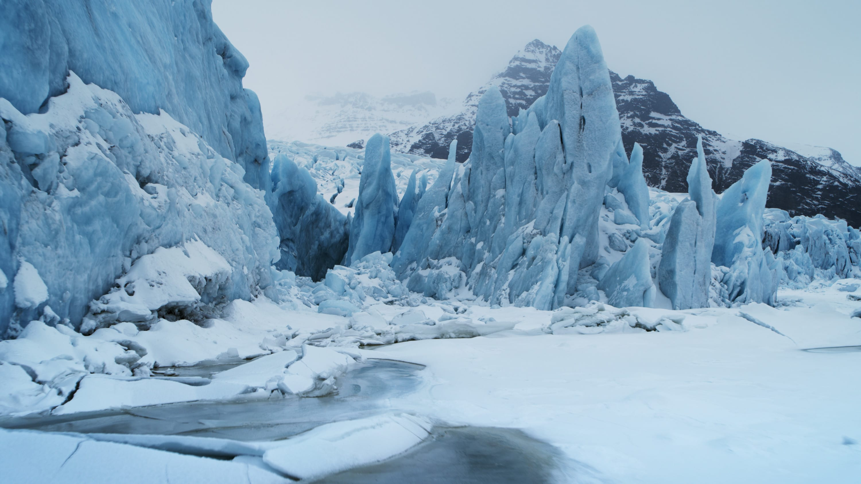 A glacier in Jökulsárlón National Park with mountains in the distance. (National Geographic for Disney+)