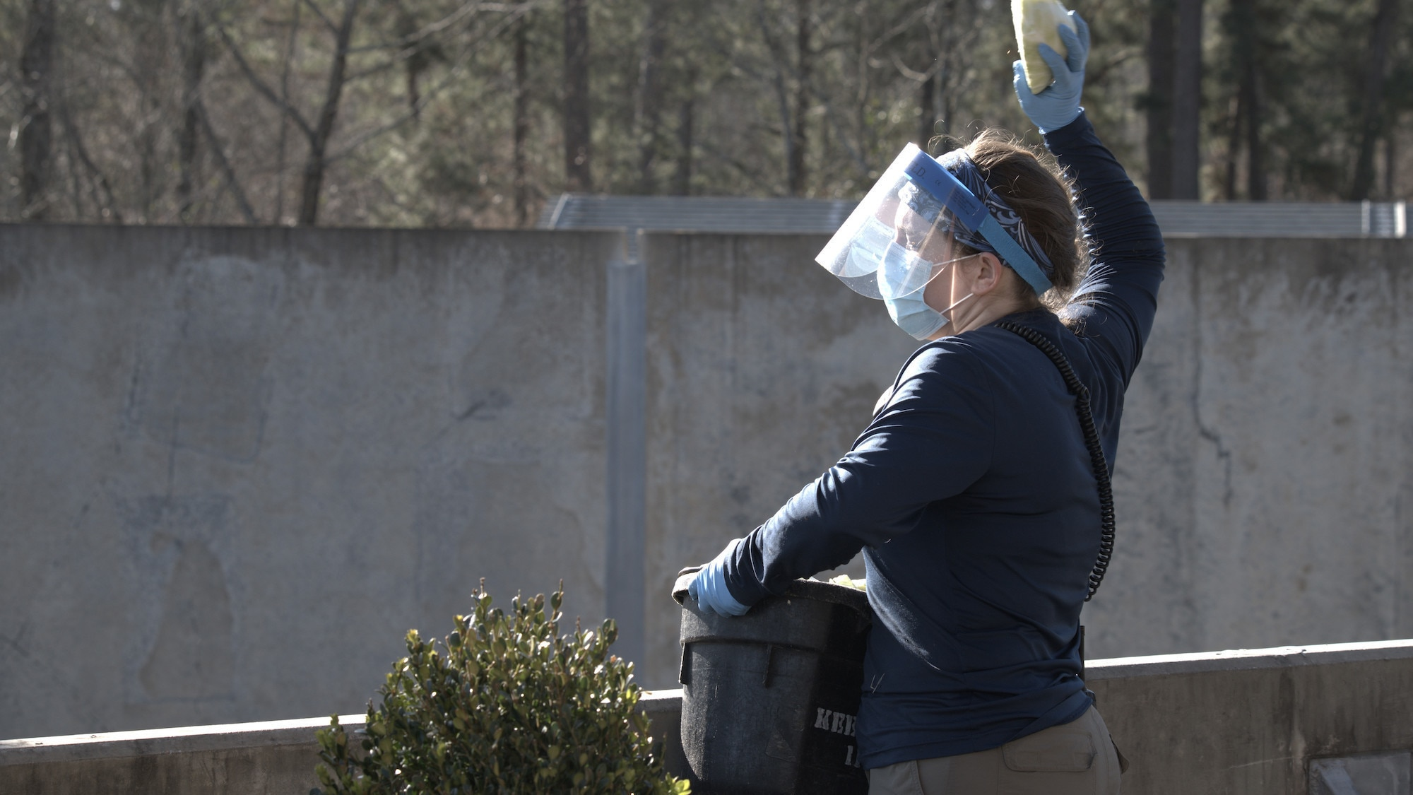 Caregiver Ellen Brady-McGaughey in PPE overlooking enclosure with bucket of cabbages. (National Geographic/Virginia Quinn)