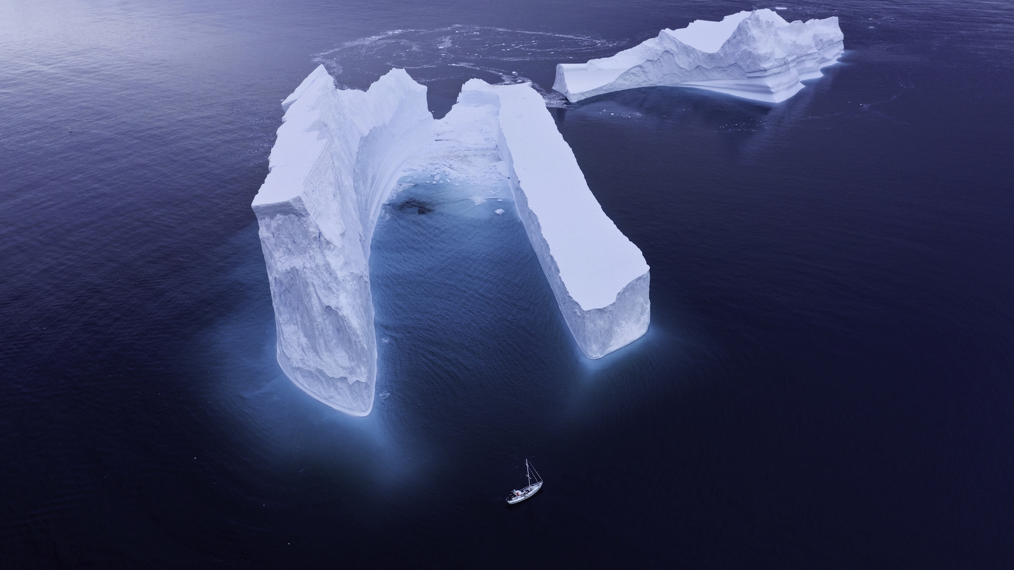 Antarctic icebergs dwarfed the team's expedition vessel, The Australis, while the team filmed humpbacks at the bottom of the world. (National Geographic for Disney+/Hayes Baxley)