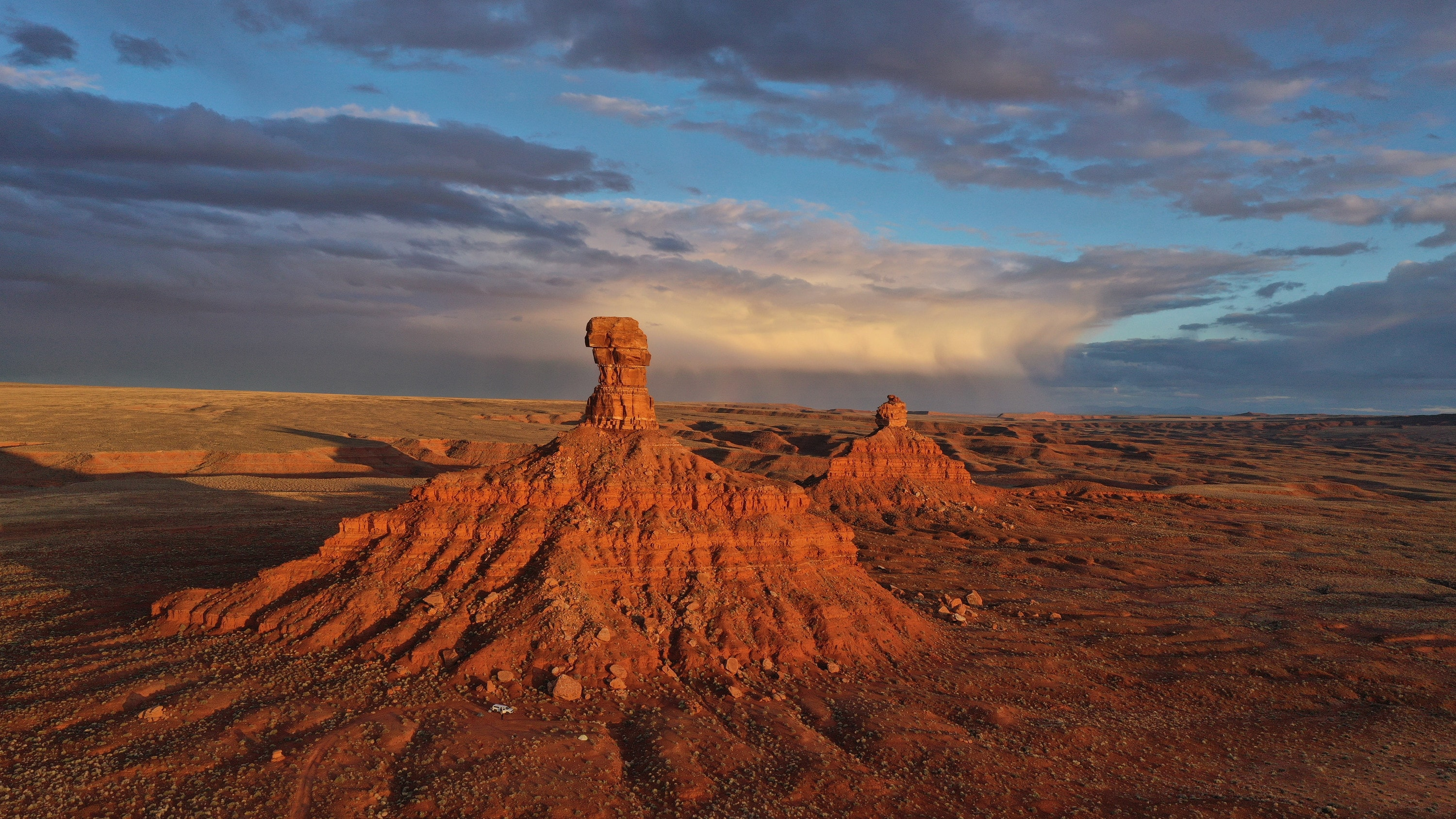 A pair of bluffs painted orange by the setting sun in Valley of the Gods, Utah. (National Geographic for Disney+/Renan Ozturk)