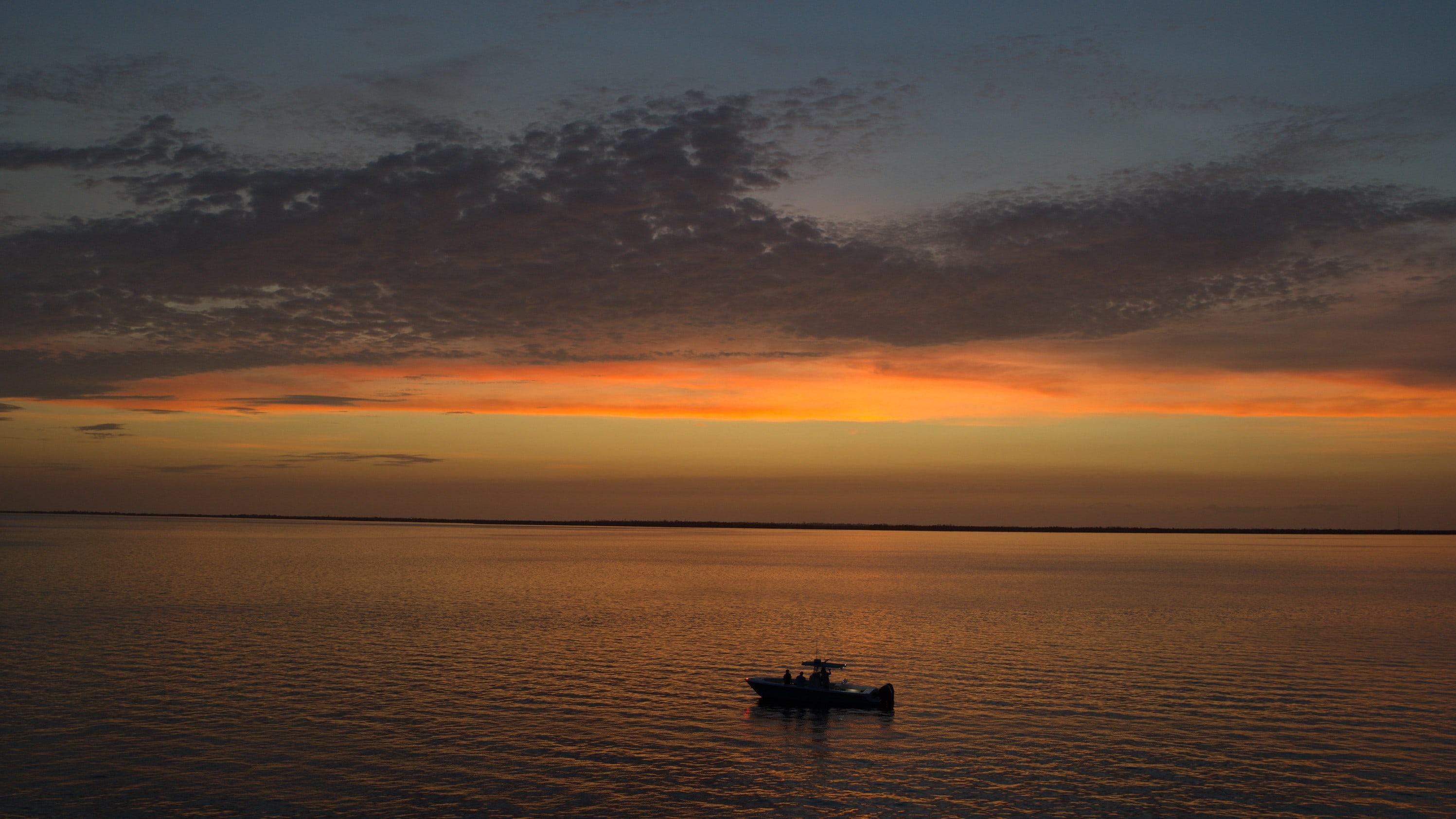 A boat out on the ocean side of the Florida Keys, against an orange sunset. (National Geographic for Disney+)