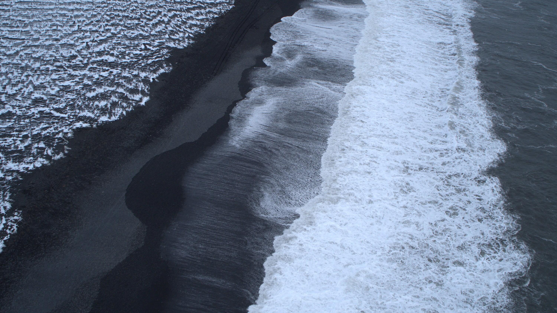 Ocean waves crash onto the black sand of Reynisfjara Beach. (National Geographic for Disney+)