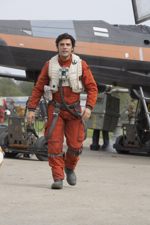 Oscar Isaac as Poe Dameron walking in orange resistance flight suit.