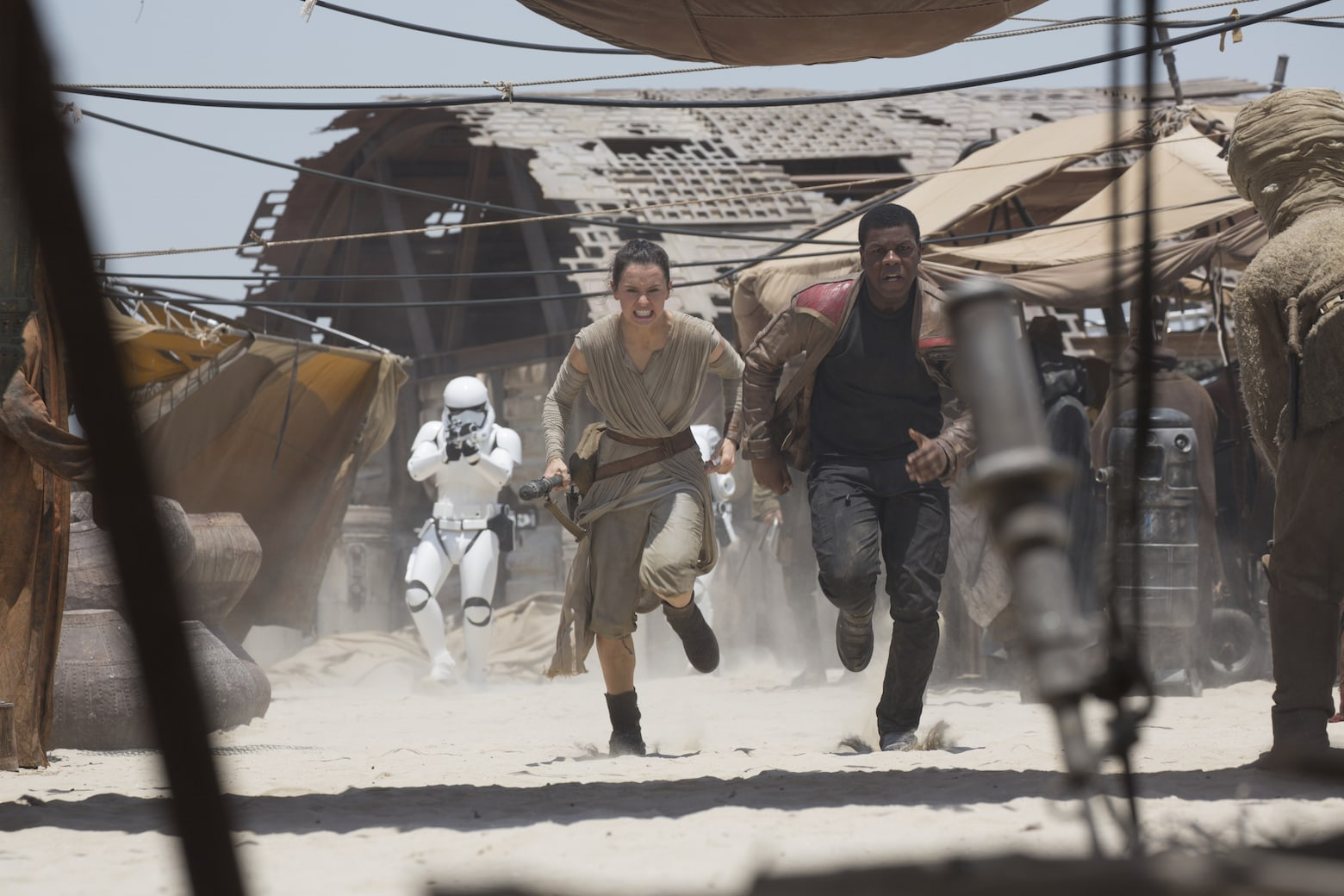 Rey and Finn run from First Order stormtroopers.