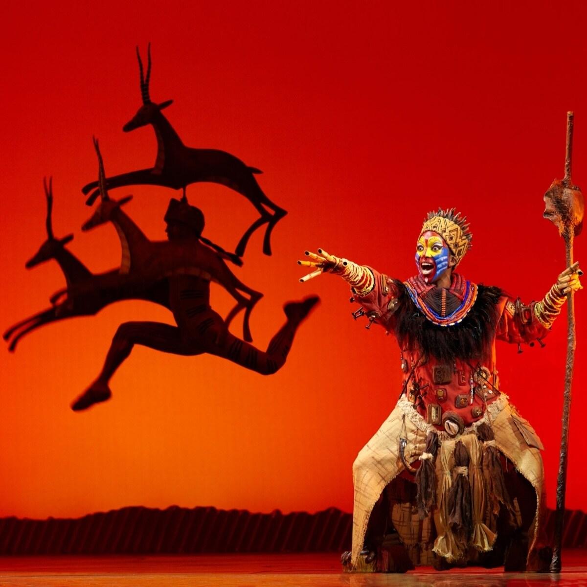 Rafiki cantando en el escenario sobre un fondo rojo con siluetas de gacelas