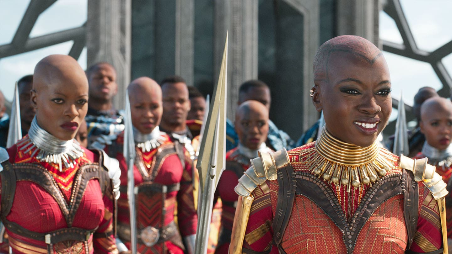 Okoye (Danai Gurira) smiling and standing in front of a crowd of soldiers