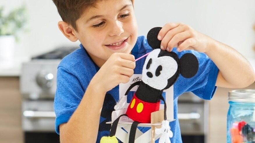 Garçon cousant une peluche Mickey Mouse.
