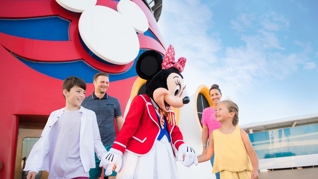 Family walking with Minnie Mouse on a Disney cruise ship
