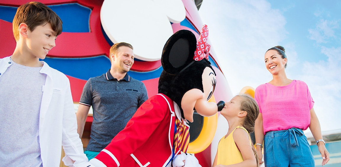 Minnie Mouse greeting a happy family on-board the Disney Cruise Line