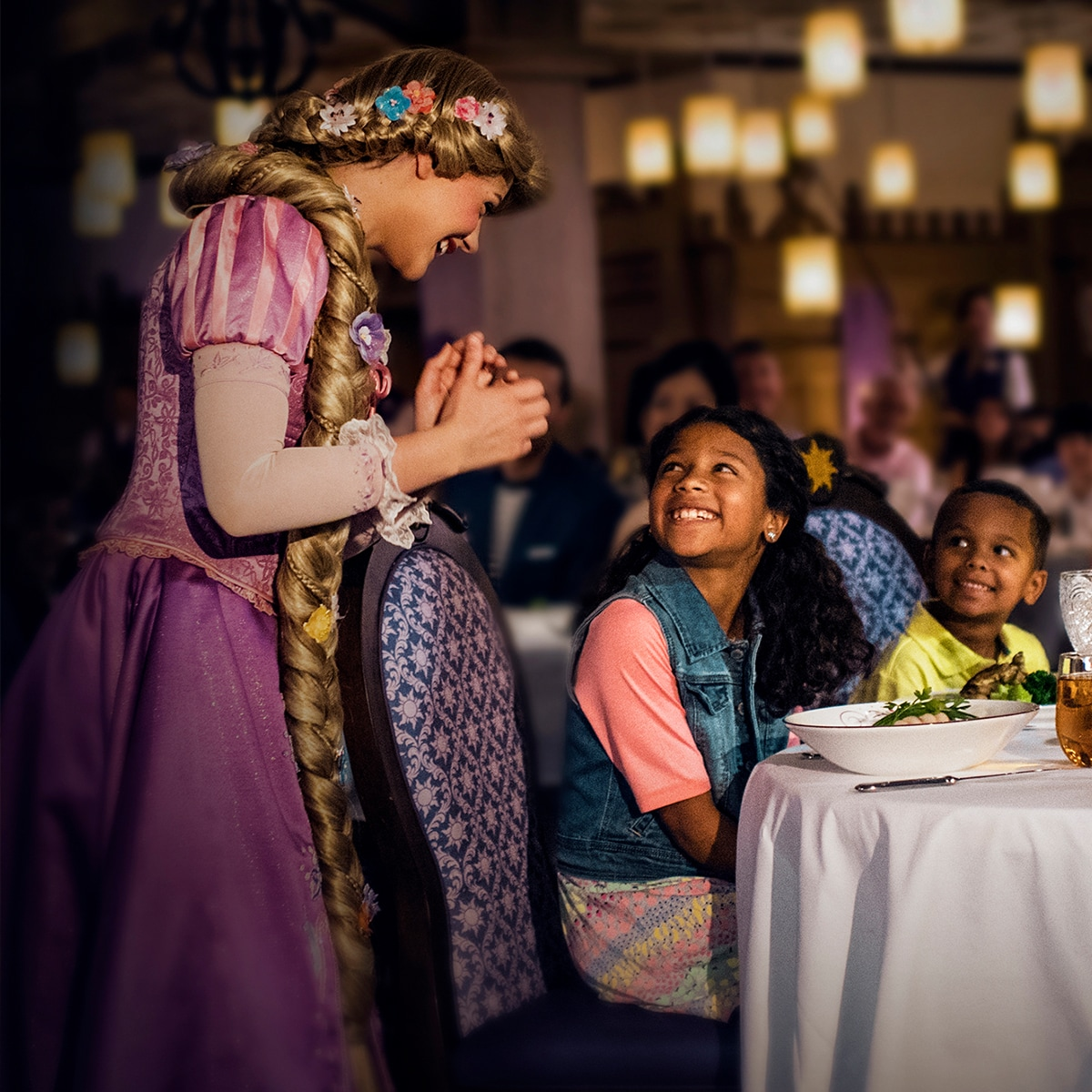 Rapunzel greeting a family who are eating dinner