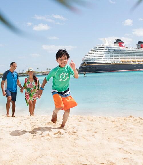 Familie op het strand met Disney-cruise op de achtergrond.